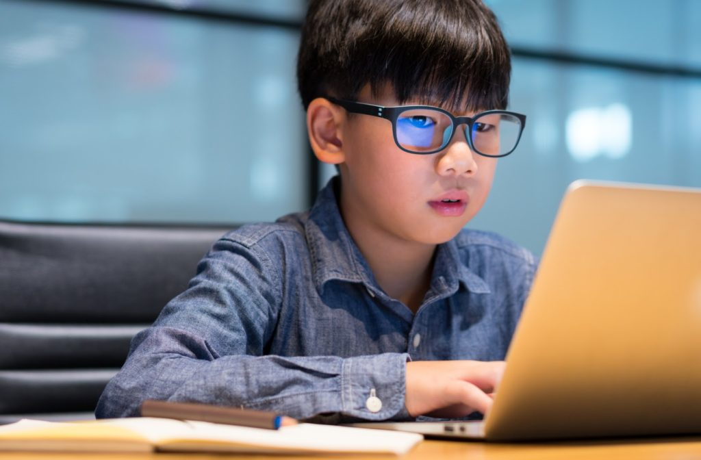 Child wearing blue light glasses as he works on his laptop.
