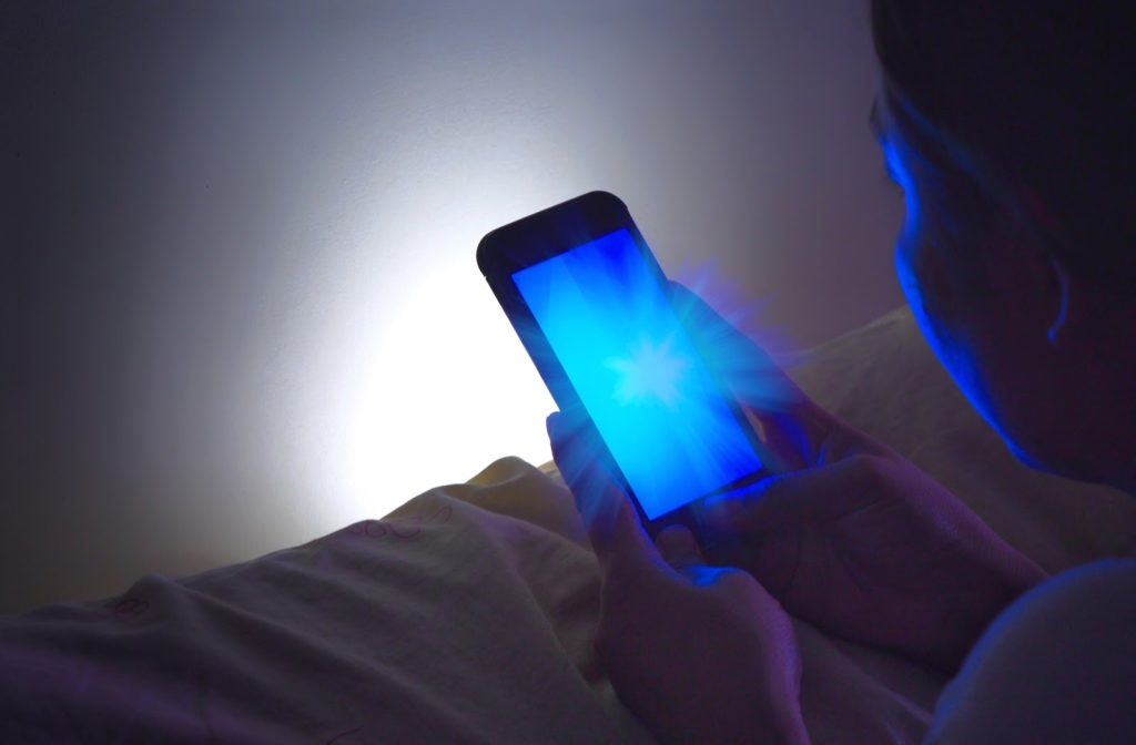 blue light shinning on girl using her phone while laying on her bed.